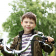 Boy on a bicycle in the green park - Stok fotoğraf