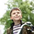 Boy on a bicycle in the green park - Stock Photo