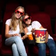 Two young girls watching in cinema — Stock Photo #6730617