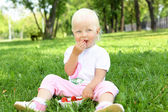 Little girl with strawberries outdoors — Stock Photo