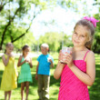 Girl drinking milk in the summer park - Stock Photo
