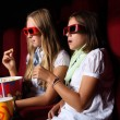 Two young girls watching in cinema — Stock Photo #6741541