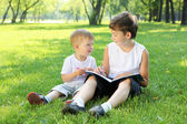 Children in the park reading a book — Stok fotoğraf