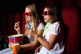 Two young girls watching in cinema — Стоковое фото