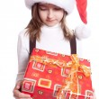 Stock Photo: Little girl with santa's hat and gift holding