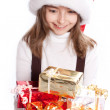 Little girl with santa's hat. Sitting and holding the gift — Stock Photo #5781988