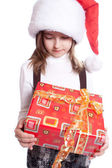 Little girl with santa's hat and gift holding — Stock Photo