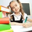 Stock Photo: School girl sitting at table with books.