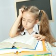 Stock Photo: School girl making homework behind stack of books.