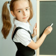 Stock Photo: School girl near blank blackboard. Ready for writing.