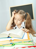 School girl making homework behind stack of books. — Stock Photo