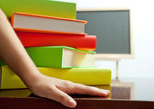 Hand and stack of colored book on the table — Stock Photo