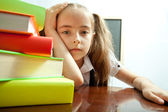 Tired school girl behind stack of books — Stock Photo