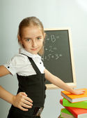 School girl front blackboard with hand on stack of books. — Stock Photo