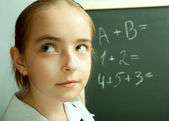 Schoolgirl thinking about exercises written on the blackboard — Stock Photo