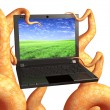 Tentacles of a monster, holding a laptop — Stock Photo