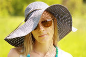 Beautiful blonde girl in hat and spectacles — Stock Photo