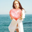 Portrait beautiful girl keeps air ball in form heart — Stock Photo