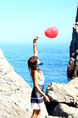 Flicka håller luft ball nära havet — Stockfoto