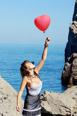 Beautiful girl keeps air ball near sea — Stock Photo