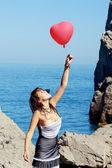 красивая девушка держит воздушный шар возле моря — Стоковое фото
