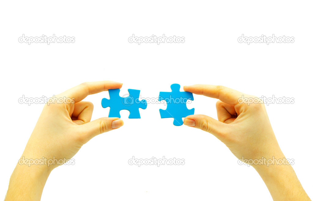 Woman fingers holdings gold puzzle on white — Stock Photo #5417536