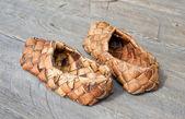 Antico russo sandali di corteccia sul pavimento in legno — Foto Stock