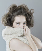 Young girl hiding behind a fur hood. — Stock Photo