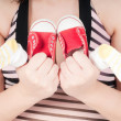 Portrait of pretty pregnant woman baby shoes — Stock Photo #5465619
