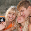 Girls and boy with camera on a beach — Stock Photo