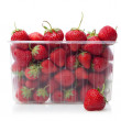 Fresh strawberries in plastic box on white. — Stockfoto