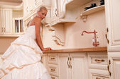 Beautiful bride stands in the kitchen — Stock Photo