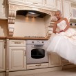 Beautiful bride stands in the kitchen - Stock Photo