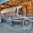 Old wooden coach wheels around a barn. - Stock Photo