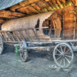 Old wooden coach wheels around a barn. — Stock fotografie