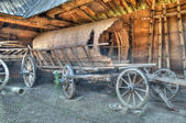 Old wooden coach wheels around a barn. — Stock Photo