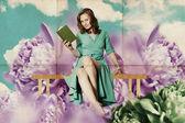 Mooie vrouw met boek in bloemen — Stockfoto