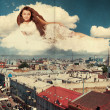 Beauty woman in the clouds over city - Stock Photo