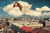 Beauty woman in the clouds over city — Stock Photo
