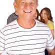 Handsome old man in focus with family in the background — Stock Photo