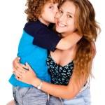 Young kid kissing his mom and looking at camera — Stock Photo