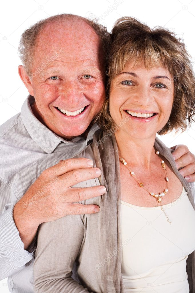 Attractive old couple posing as man hugs his wife from behind, isolated on white background.  Stock Photo #5944423