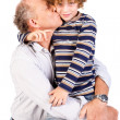 Stock Photo: Grandson kissing his grandfather