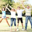 Family jumping with wide-spread raised arms — Stock Photo