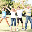 Stock Photo: Family jumping with wide-spread raised arms