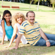 Stock Photo: Young family relaxing in park