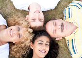 Happy family of four on grass — Stock Photo