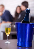 Champagne in focus, couples in background — Stock Photo