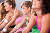 Group of four spinning in gym — Stock Photo