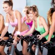 Attractive females on bicycles in a fitness club — Stock Photo